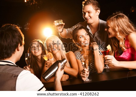 Photo of joyful friends in the bar communicating with each other - stock photo