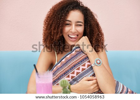 Photo of joyful funny African American dark skinned female has frizzy hair, blinks eye and shows tongue, foolishes in cafe with friends, orders fresh smoothie, sits on blue sofa with cushion