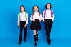 Photo of joyful school children stroll back to school wear rucksack uniform shoes isolated blue color background