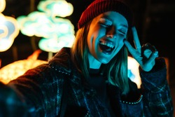 Photo of joyful woman gesturing peace sign and taking selfie photo while walking at park with neon lighting
