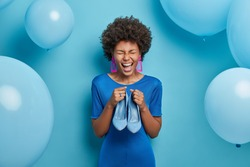 Photo of joyful woman rejoices buying new outfit, holds blue stylish shoes to fit dress, dresses on special occasion, going to celebrate birthday. Blue color prevails. Fashion and clothing concept