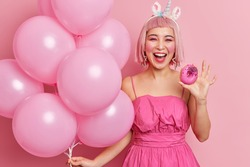 Photo of joyful young Asian woman has pink hair wears festive dress holds delicious glazed donut and bunch of inflated balloons enjoys party time isolated over rosy background. Holidays concept