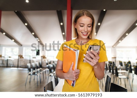 Photo of joyful young woman holding exercise books and cellphone while standing in open-plan office