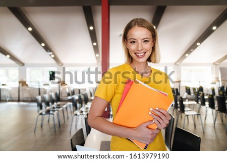 Photo of joyful young woman holding exercise books and smiling while standing in open-plan office