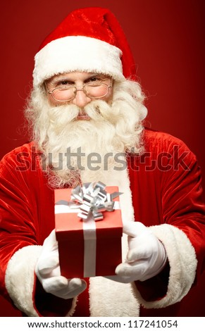 Photo of kind Santa Claus giving xmas present and looking at camera