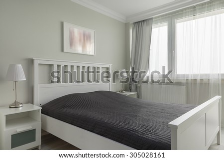 Photo of king size white wooden bed with black bedding