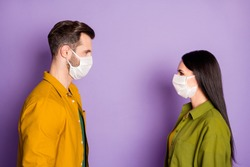 Photo of lady guy couple stand distance opposite look eyes negative attitude close contact corona virus pandemic infection wear protective mask shirts isolated purple color background