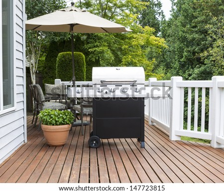 Photo of large barbecue cooker on cedar deck with patio furniture and trees in background   #147723815