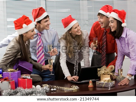 Photo of laughing co-workers interacting during corporate party in office