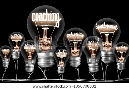 Photo of light bulbs group with shining fibers in a shape of Coaching concept related words isolated on black background #1358908832