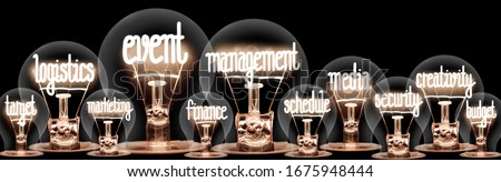 Photo of light bulbs group with shining fibers in a shape of Event Management, Logistics, Target, Creativity and Media concept related words isolated on black background