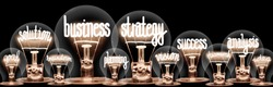 Photo of light bulbs with shining fibers in a shape of Business Strategy, Solution, Success, Analysis and Planning concept related words isolated on black background