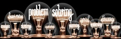 Photo of light bulbs with shining fibers in a shape of Problem Solving, Business, Goal, Efficiency and Idea concept related words isolated on black background