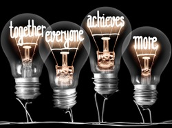 Photo of light bulbs with shining fibers in a shape of TOGETHER, EVERYONE, ACHIEVES, MORE concept words isolated on black background