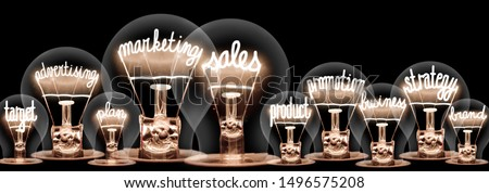 Photo of light bulbs with shining fibers in shapes of Marketing Sales, Advertising, Promotion and Strategy concept related words isolated on black background