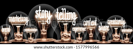 Photo of light bulbs with shining fibers in shapes of Story Telling, Marketing, Content and Creativity concept related words isolated on black background