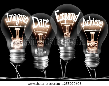 Photo of light bulbs with shining fibres in IMAGINE, DARE, EXPAND and ACHIEVE shape on black background; concept of Idea #1255070608