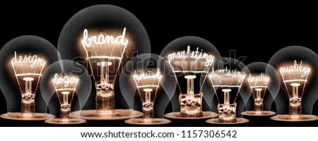 Photo of light bulbs with shining fibres in shape of BRAND concept related words isolated on black background