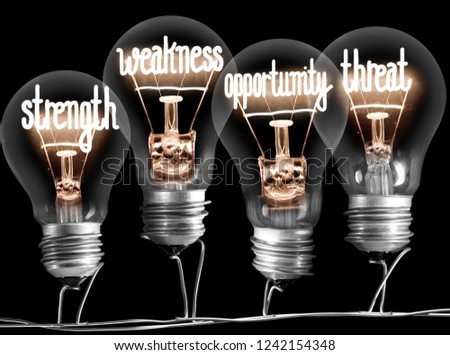 Photo of light bulbs with shining fibres in STRENGTH, WEAKNESS, OPPORTUNITY and THREAT shape on black background; SWOT analysis concept #1242154348