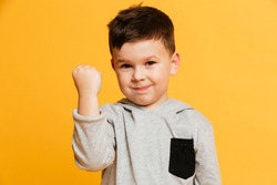Photo of little boy child standing isolated over yellow background. Looking camera gesturing with hand.