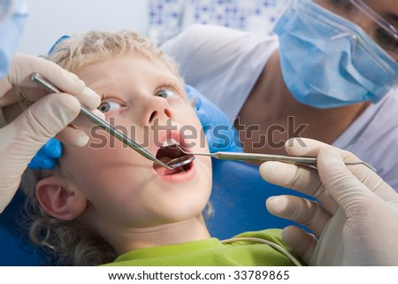 Photo of little boy having mouth checkup in dental clinic