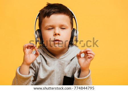 Photo of little concentrated boy child sitting on floor isolated over yellow background with eyes closed listening music with headphones.