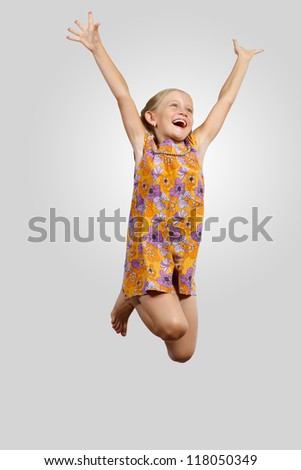 Photo of little girl jumping and raising hands against grey background
