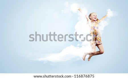 Photo of little girl jumping and raising hands against light background - stock photo