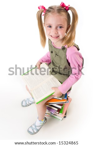 Photo of little girl with book in hands looking at camera happily