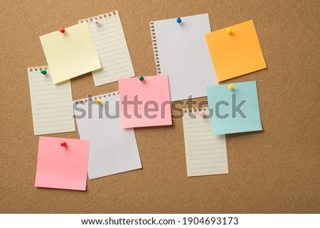 Photo of lot many colorful stickers and paper from copybooks attached to the wooden board with colorful pins Stock photo ©