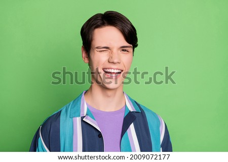 Photo of lovely brunet young guy blink wear striped shirt isolated on green color background Stock photo ©