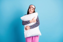 Photo of lovely charming young girl love sleep closed eyes hug pillow smiling, miss relax after long work day wear mask dotted shirt pajamas sleepwear isolated blue color background