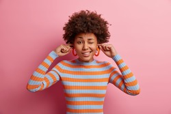 Photo of lovely curly haired young woman winks eye and plugs ears avoids hearing very loud music dressed in casual striped jumper poses against pink background. Turn sound off. Noisy atmosphere