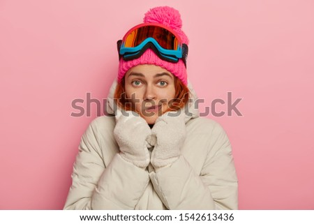 Photo of lovely European female traveler purses lips, warms herself in comfortable outerwear during winter time, wears ski mask, enjoys sunny weather in mountains and leasure outdoor activities