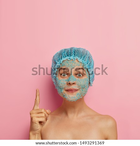 Photo of lovely European woman has blue spa salt granules on face, wears waterproof headgear, points with index finger upwards, demonstrates copy space for your promotion, isolated on pink wall
