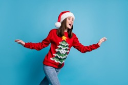 Photo of lovely pretty lady amazed look empty space raise hands running open mouth shocked wear santa x-mas headwear red ornamented sweater jeans isolated blue color background