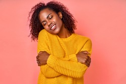 Photo of lovely smiling black woman embraces herself, has high self esteem, closes eyes from enjoyment, likes her new comfortable soft yellow sweater, tilts head, stands indoor. Love yourself concept.