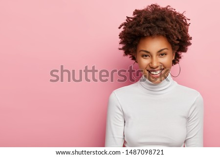 Photo of lovely young lady has curly Afro hair, smiles gently, wears earrings and white jumper, being satisfied with getting new job position, has pleasant talk with colleague, stands over pink wall