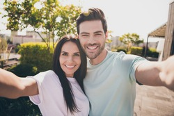 Photo of lovers couple take selfie look camera toothy shiny smile wear casual clothes in garden park outdoors