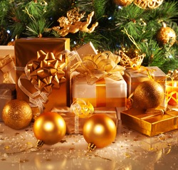 Photo of luxury gift boxes under Christmas tree, New Year home decorations, golden wrapping of Santa presents, festive fir tree decorated with garland, baubles and angels, traditional celebration