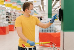 Photo of male consumer uses touchscreen in shop, checks price, poses with shopping cart, wears disposable mask and gloves, pays with self checkout. Coronavirus pandemic, safety, protective measures