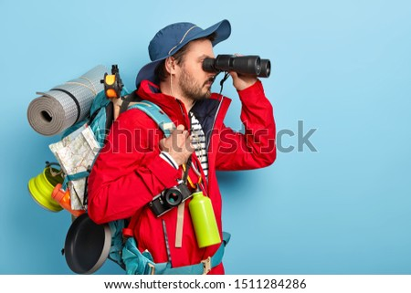 Photo of male explorer dressed in casual wear, keeps binoculars near eyes, wears hat and jacket, hikes in mountains, isolated over blue background copy space area for your advertisement. Tourist hiker