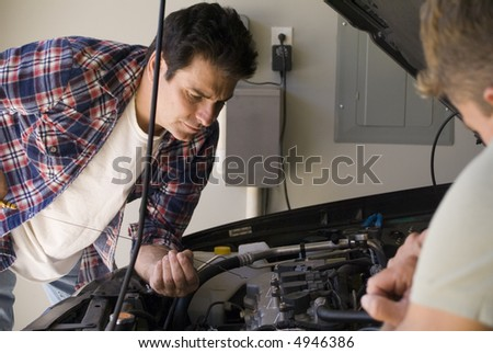 Photo of man checking oil in car