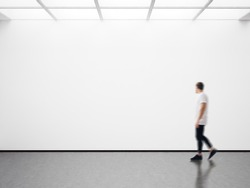 Photo of man in modern gallery looking at the empty canvas. Blank mockup, motion blur