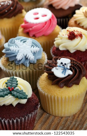 Photo of many cupcakes decorated for Christmas. Focus on snowman. - stock photo
