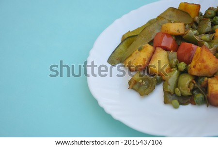 Photo of matar paneer mix veg (Indian food) on white plate isolated over light blue background with copy space  Foto stock ©