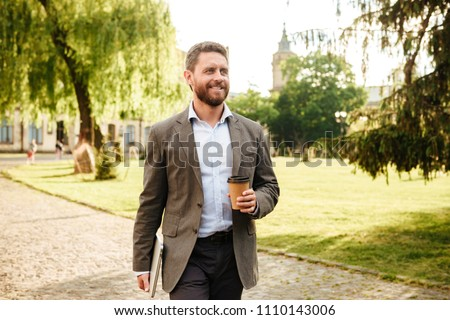Photo of mature joyous man in gray classical suit walking along park carrying takeaway coffee and silver laptop