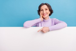 Photo of mature woman happy positive smile indicate finger white poster empty space recommend promo isolated over blue color background