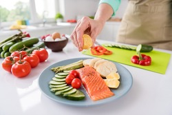 Photo of mature woman squeeze lemon juice dish cook gourmet salmon vegetables diet cafe delicious food indoors