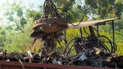 Photo of metal scrap and waste stcking to the electric magnet on dump